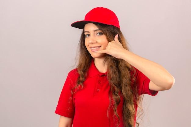 赤いポロシャツと分離の白い背景の上に自信を持って探しているジェスチャーを呼んでキャップを身に着けている若い配達の女性