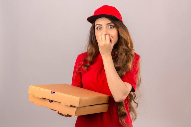 赤いポロシャツとキャップを身に着けている若い配達女性緊張と分離の白い背景の上の口に手を入れて怖い