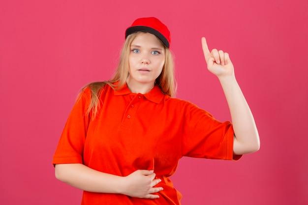 격리 된 분홍색 배경 위에 검지 손가락으로 좋은 아이디어 개념을 가리키는 빨간색 폴로 셔츠와 모자를 쓰고 젊은 배달 여자