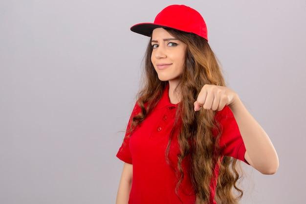 赤いポロシャツと分離の白い背景に優しい笑みを浮かべて拳バンプを示すキャップを着ている若い配達の女性