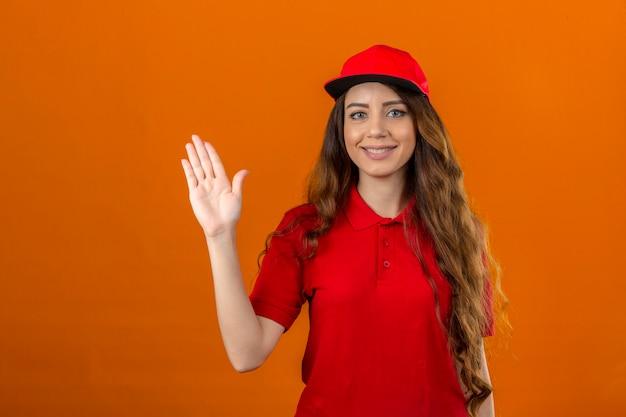 赤いポロシャツと帽子を着て幸せそうに笑って元気に手を振って歓迎の挨拶や孤立したオレンジ色の背景にさようならを言う若い配達の女性