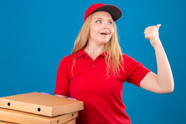 赤いポロシャツと孤立した青い背景に側に驚いた人差し指を探しているピザの箱で立っているキャップを着ている若い配達の女性