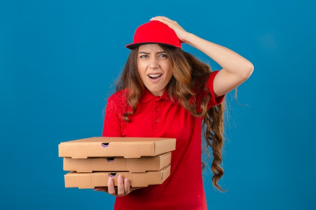 誤解のために頭に手でショックを受けた赤いポロシャツとピザの箱で立っているキャップを着ている若い配達の女性は、孤立した白い背景の上のエラーを忘れたエラーを忘れてしまった
