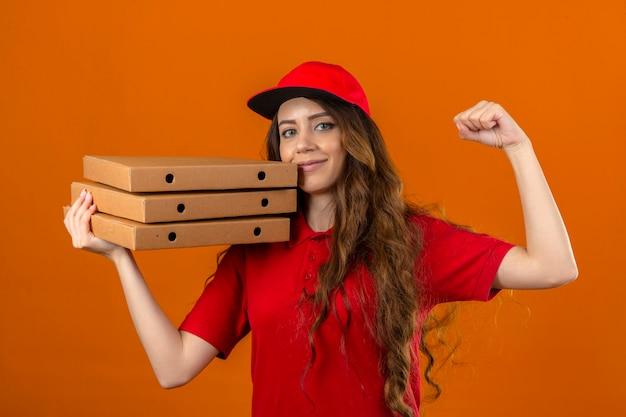 孤立したオレンジ色の背景の上に自信を持って勝者の概念を探している拳を上げる肩にピザの箱のスタックで赤いポロシャツとキャップ立って身に着けている若い配達の女性