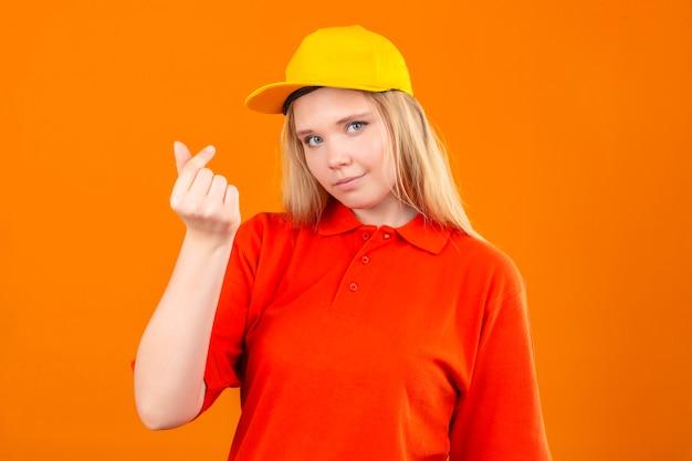 Молодая курьерская женщина в красной рубашке поло и желтой кепке делает денежный жест, улыбаясь на изолированном оранжевом фоне