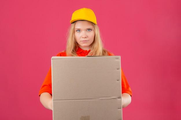 赤いポロシャツと分離のピンクの背景に深刻な顔でカメラを見て段ボール箱を保持している黄色の帽子を着ている若い配達の女性