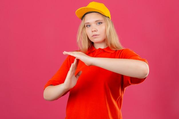 Молодая курьерская женщина в красной рубашке поло и желтой кепке выглядит перегруженной, делая жест тайм-аута руками на изолированном розовом фоне