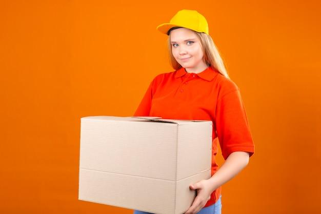 赤いポロシャツと分離のオレンジ色の背景に優しい笑顔の段ボール箱で立っている黄色の帽子を着ている若い配達の女性