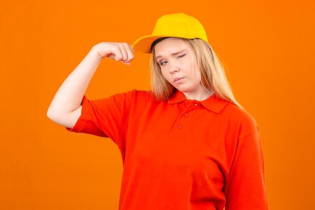 Молодая женщина-доставщик в красной рубашке поло и желтой кепке, подмигивая, стоя с поднятым кулаком победителя концепции на изолированном оранжевом фоне