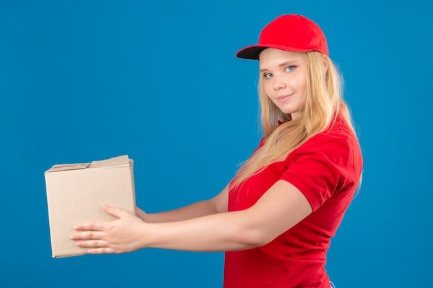 Giovane donna delle consegne indossando maglietta polo rossa e cappuccio dando scatola di cartone a un cliente che guarda fiducioso su sfondo blu isolato