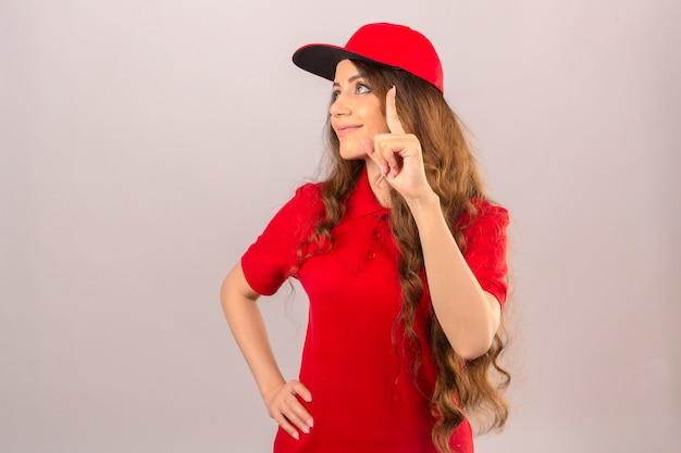 Giovane donna delle consegne che indossa la maglietta polo rossa e cappuccio alzando lo sguardo e puntando il dito sorridente su sfondo bianco isolato