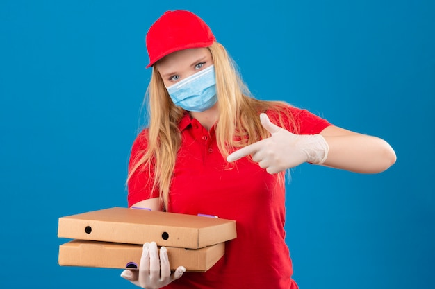 Young delivery woman wearing red polo shirt and cap in medical protective mask standing with pizza boxes pointing with finger to them looking at camera with serious face over isolated blue back