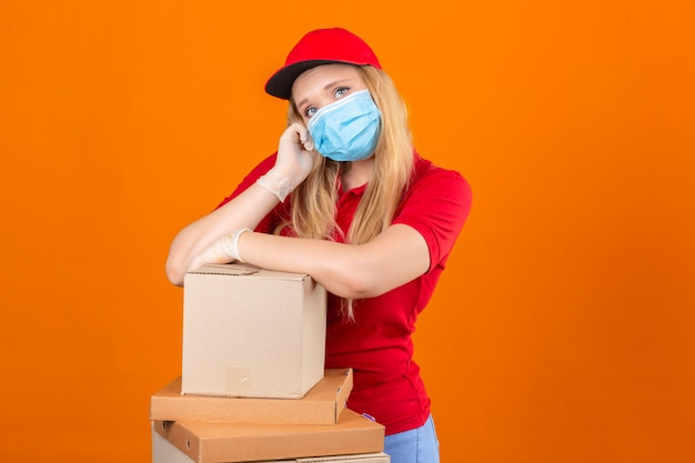 Young delivery woman wearing red polo shirt and cap in medical protective mask waiting holding hand on cheek while support it with another crossed hand with stack of cardboard boxes looking tired