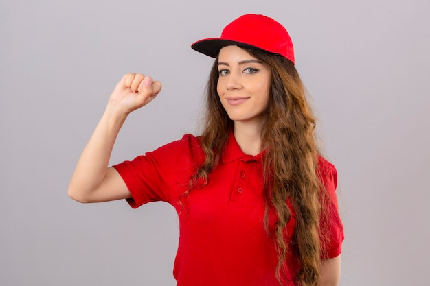 Young delivery woman wearing red polo shirt and cap raising fist after a victory happy face winner concept over isolated white background