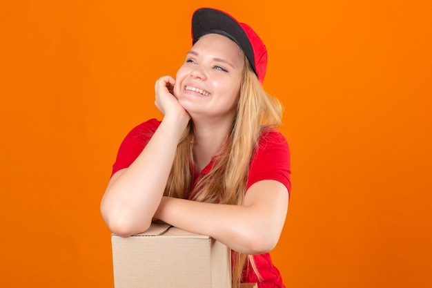 Young delivery woman wearing red polo shirt and cap smiling waiting holding hand on cheek while support it with another crossed hand looking confident and happy over isolated orange background