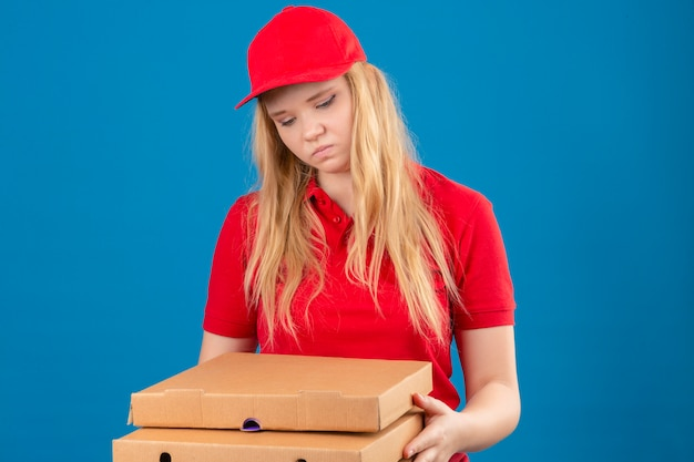 Young delivery woman wearing red polo shirt and cap standing with pizza boxes looking sad and bored with unhappy face over isolated blue background