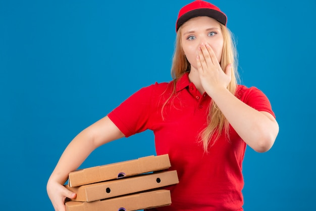 Young delivery woman wearing red polo shirt and cap standing with pizza boxes shocked covering mouth with hand over isolated blue background