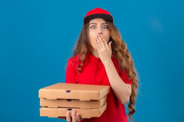 Young delivery woman wearing red polo shirt and cap standing with pizza boxes shocked covering mouth with hand with wide opened eyes over isolated blue background
