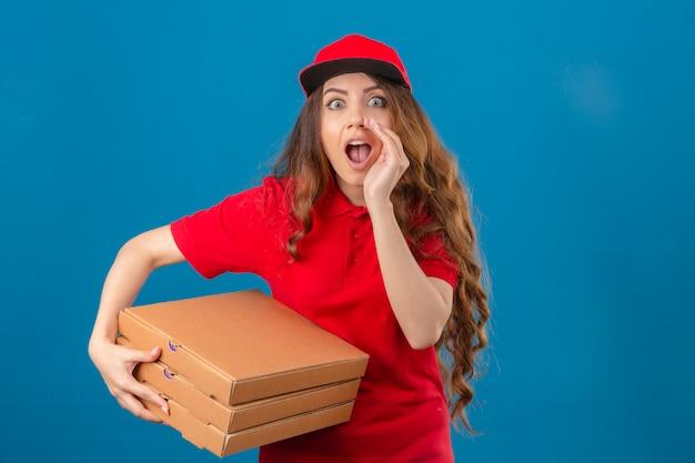 Giovane donna delle consegne che indossa la maglietta polo rossa e cappuccio in piedi con scatole per pizza gridando a lato con la mano sulla bocca guardando sorpreso su sfondo blu isolato