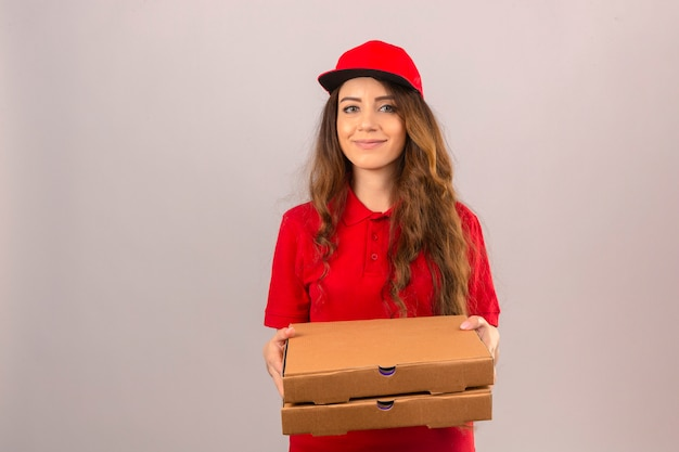 Young delivery woman wearing red polo shirt and cap standing with pizza boxes smiling friendly over isolated white background