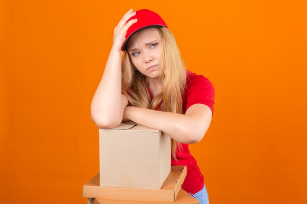 Young delivery woman wearing red polo shirt and cap waiting holding hand on head while support it with another crossed hand with stack of cardboard boxes looking tired and sick over isolated o