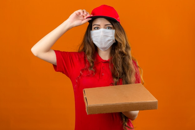 Young delivery woman wearing red polo shirt in medical protective mask putting on cap standing with stack of pizza boxes looking confident over isolated orange background