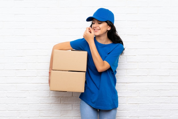 Young delivery woman over white brick wall smiling a lot