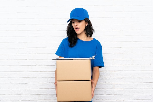 Young delivery woman over white brick wall