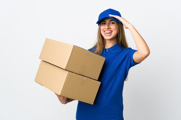 Young delivery woman over white wall saluting with hand with happy expression