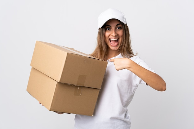 Young delivery woman over white wall with surprise facial expression