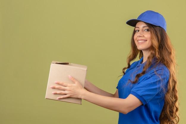 青いポロシャツと孤立した緑の背景に笑みを浮かべて顧客に段ボール箱を与えるキャップを身に着けている巻き毛の若い配達の女性