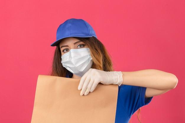 격리 된 분홍색 배경 위에 심각한 얼굴로 카메라를 찾고 종이 패키지를 들고 의료 보호 마스크와 장갑에 파란색 폴로 셔츠와 모자를 쓰고 곱슬 머리를 가진 젊은 배달 여자
