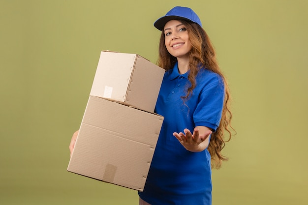 파란색 폴로 셔츠를 입고 곱슬 머리를 가진 젊은 배달 여자와 격리 된 녹색 배경 위에 배달을 위해 지불을 기다리는 미소로 카메라를보고 골판지 상자와 서 모자