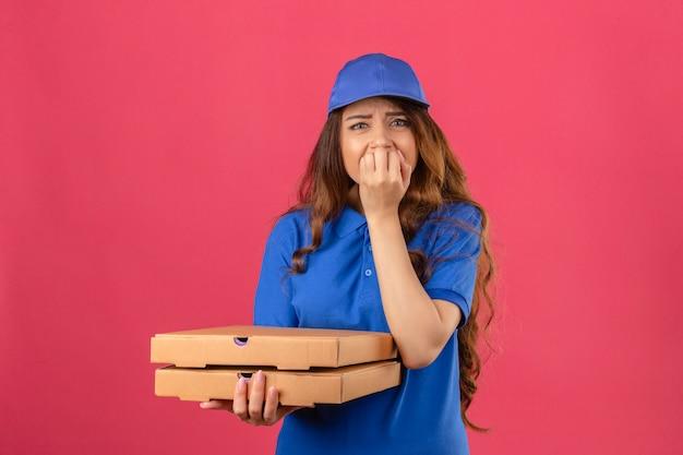 分離されたピンクの背景の上に爪をかむ口に手でストレスと緊張しているピザの箱で立っている青いポロシャツとキャップ立っている巻き毛の若い配達の女性