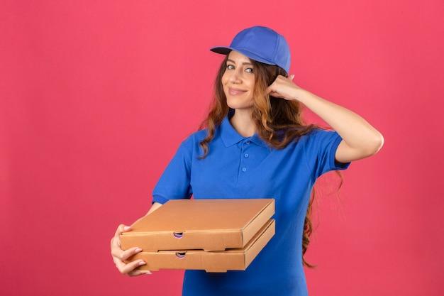 分離されたピンクの背景に自信を持って探しているジェスチャーを呼び出すジェスチャーを作る青いポロシャツとピザの箱で立っているキャップを身に着けている巻き毛の若い配達の女性