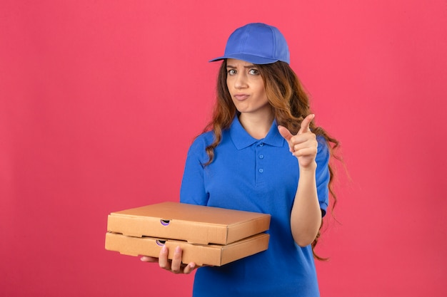 青いポロシャツと孤立したピンクの背景にカメラの懐疑的な表現を指で指しているピザの箱で立っているキャップを身に着けている巻き毛の若い配達の女性