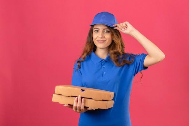 青いポロシャツと分離のピンクの背景に自信を持って探している敬礼のピザの箱で立っているキャップを着ている巻き毛の若い配達の女性