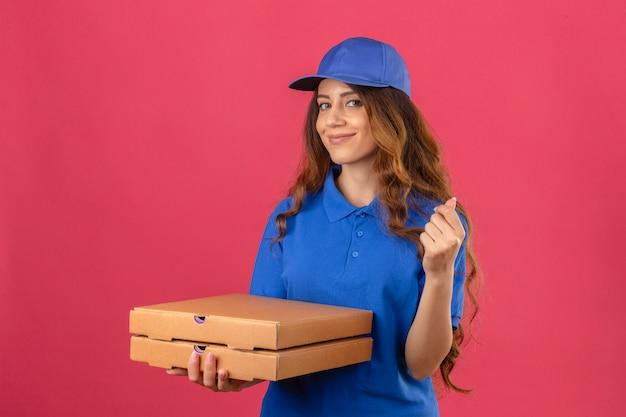 Молодая доставщица с вьющимися волосами в синей рубашке поло и кепке, стоящая с коробками для пиццы, обеспокоенная деньгами, делает денежный жест рукой, улыбаясь на изолированном розовом фоне