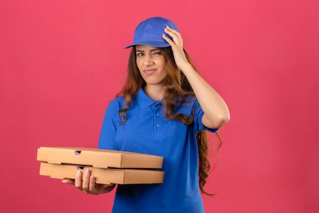 青いポロシャツとキャップを身に着けている巻き毛の若い配達の女性は誤って頭の上の手で驚いた