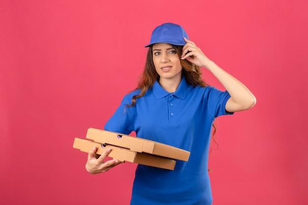青いポロシャツを着た巻き毛の若い配達の女性と誤って頭の上の手でキャップは、分離されたピンクの背景にエラーを忘れたエラーを忘れてしまった