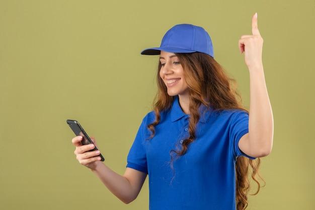 Giovane donna delle consegne con capelli ricci che indossa la maglietta polo blu e cappuccio guardando smartphone sorridente puntare il dito verso l'alto su sfondo verde isolato