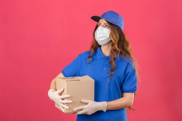 Giovane donna di consegna con capelli ricci che indossa la maglietta polo blu e il cappuccio in maschera protettiva medica e guanti cercando in piedi con la scatola di cartone isolato su sfondo rosa