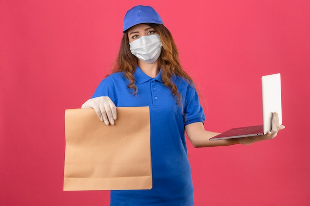 Young delivery woman with curly hair wearing blue polo shirt and cap in medical protective mask and gloves showing paper package holding laptop in other hand looking at camera with serious face ove