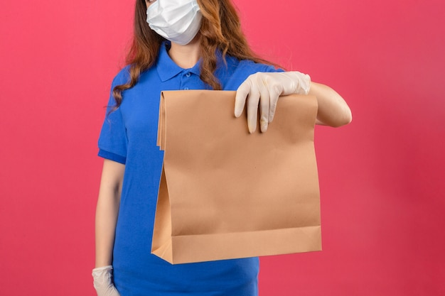 Young delivery woman with curly hair wearing blue polo shirt and cap in medical protective mask and gloves standing with paper package over isolated pink background