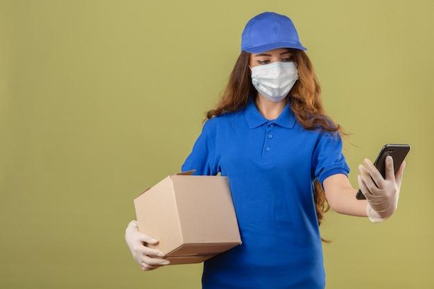 Giovane donna delle consegne con i capelli ricci che indossa la maglietta polo blu e berretto in maschera protettiva medica in piedi con la scatola di cartone e guardando lo schermo dello smartphone con la faccia seria sopra verde isolato