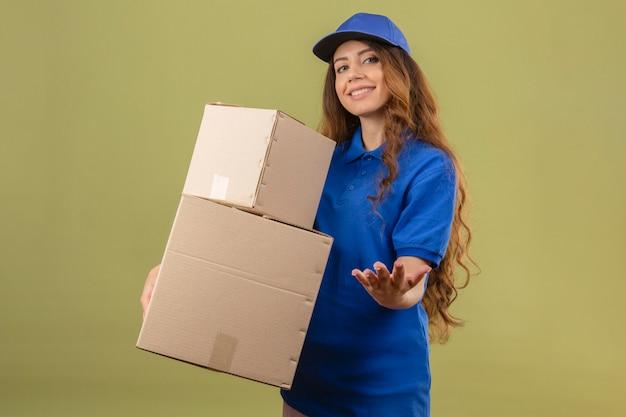 Giovane donna di consegna con capelli ricci che indossa la maglietta polo blu e cappuccio in piedi con scatole di cartone che guarda l'obbiettivo con sorriso in attesa di pagamento per la consegna su sfondo verde isolato
