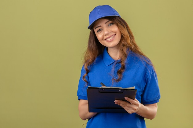 Young delivery woman with curly hair wearing blue polo shirt and cap standing with clipboard looking at camera smiling friendly over isolated green background