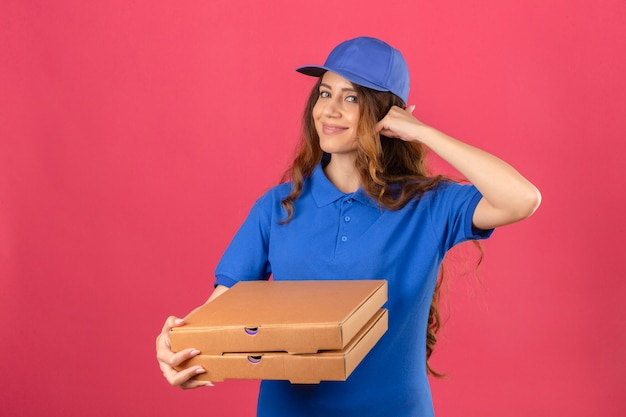 Young delivery woman with curly hair wearing blue polo shirt and cap standing with pizza boxes making call me gesture looking confident over isolated pink background
