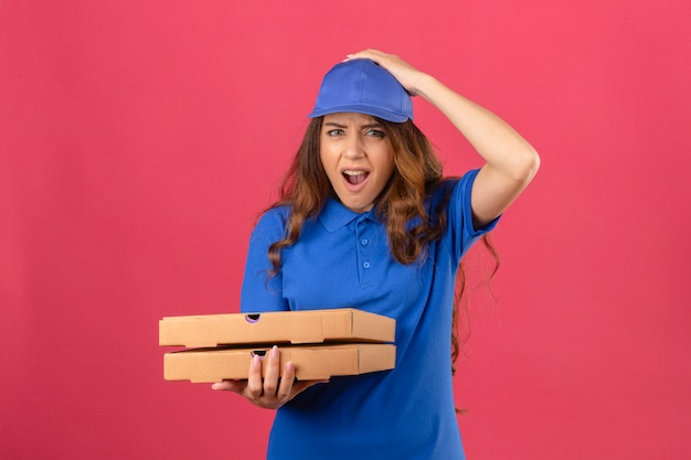 Giovane donna di consegna con i capelli ricci che indossa la maglietta polo blu e il cappuccio in piedi con scatole per pizza scioccato con la mano sulla testa per errore ricorda l'errore dimenticato il concetto di cattiva memoria su rosa isolato b