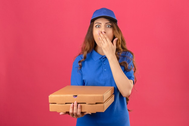 Young delivery woman with curly hair wearing blue polo shirt and cap standing with pizza boxes surprised covering mouth with hand over isolated pink background